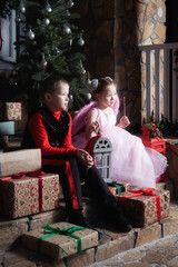 Boy and girl are sitting on the porch with gifts