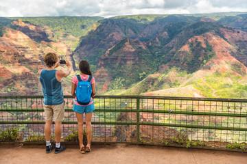 Hawaii travel couple tourists taking phone picture at Waimea Canyon nature hiking. Summer vacation people sightseeing using smartphone in Kauai, USA.