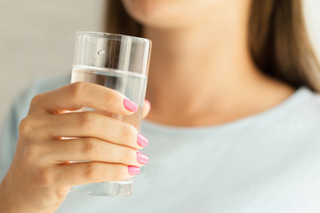 Woman holding a glass of water, close-up