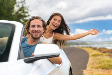Wall Mural - Car road trip couple summer fun on travel vacation freedom. Happy free people in convertible cabriolet driving. Asian woman carefree with open arms cheering joyful. Friends going on holidays.