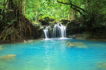 Blue lake and small waterfall. Bright exotic nature with fresh water stream.