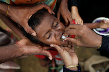 A Rohingya refugee child gets an oral cholera vaccine, distributed by WHO with the help of volunteers and local NGO's, in a refugee camp near Cox's Bazar