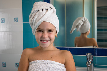 Little girl in bathroom with towel on a head.