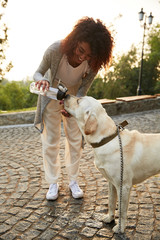 Young careless lady giving water to her pet in park