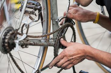 Mechanic fix the chain of a vintage bicycle