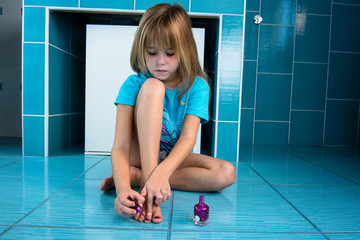 Little girl lashes her nails on her feet in bathroom.
