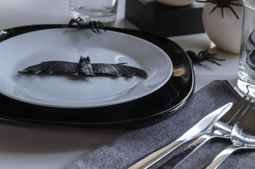 Elegant Halloween table settings in black white colors. Halloween party typical symbols bat and spiders.