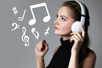 Young woman listening music with wireless headphones.