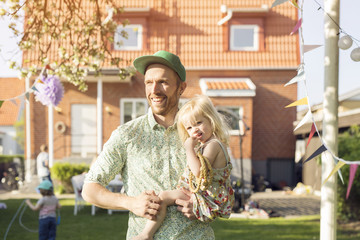 Man carrying daughter (18-23 months) in back yard