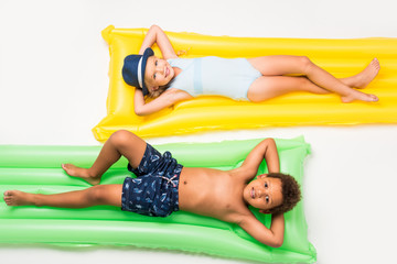 kids in swimwear on swimming mattresses