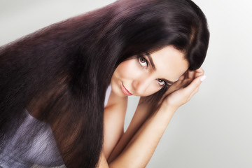 Hair beauty. Fashion. A model for a woman that touches her long and healthy brown hair. Beauty Brunette. Girl isolated on gray background. The concept of beauty.