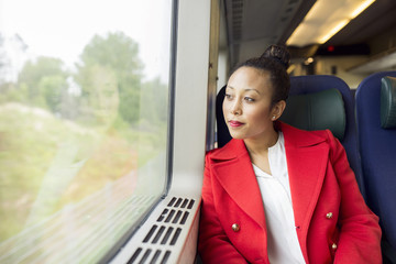 Woman in red coat sitting and looking through train window