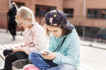 Girls (8-9) using mobile phones