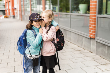 Girl whispering to friend's ear outdoors