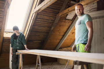 Couple working to renovate old attic