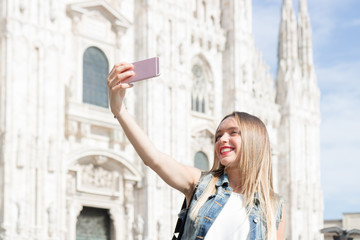 Pretty young tourist taking a selfie with her mobile phone in Milan, Italy
