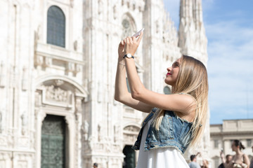 Pretty tourist teenager taking a photo with her mobile phone in Duomo square, the main landmark of Milan, Italy