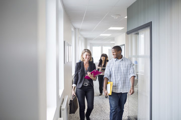 Architects and project managers walking through corridor