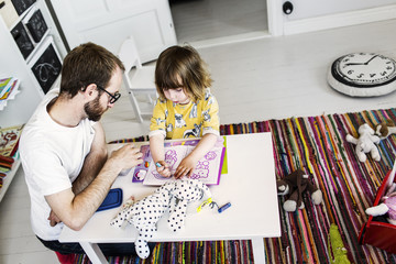 Father and daughter (2-3) drawing at table