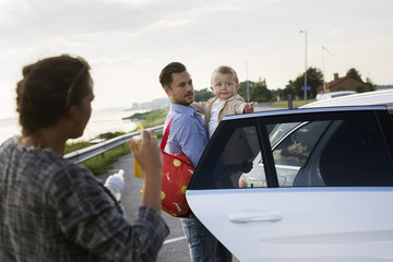 Father holding son (18-23 months) by car