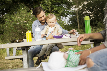 Father sitting with son (18-23 months) by picnic table