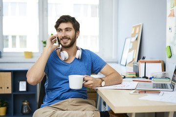 Young man sitting at desk in home office and talking on phone