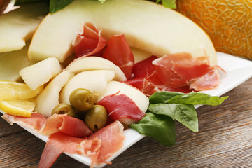 Ripe melons with jamon, olives and basil leafs on wooden table