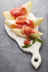 Ripe melons with jamon and basil leafs on grey wooden table