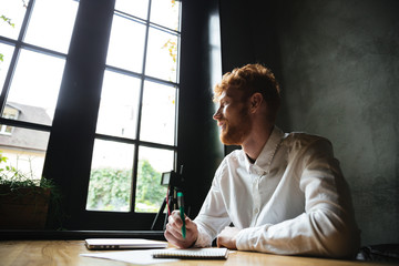 Photo of young smiling handsome readhead bearded man sitting on the workplace at home, looking at big window
