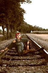 Junge Punk-Frau sitzt auf Schienen