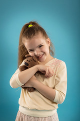 Portrait of a caucasian girl in a studio on a blue isolated background, a baby with a teddy bear in her hands
