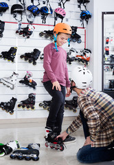 Father putting roller-skates on his son