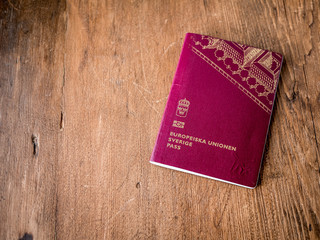 Swedish passport folded on wood rustic background.