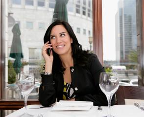 Businesswoman on mobile in restaurant