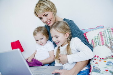 Mother and two girls looking at laptop