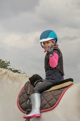 Cute little girl ride a horse and wawe with a hand.