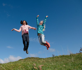 Two young girls jumping on hill