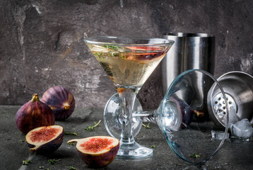 Fall and winter drinks recipes, Martini cocktail with fig, thyme and honey, on black stone table, copy space