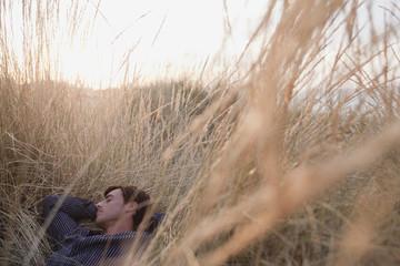 man lying in reed sleeping