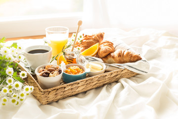 Wicker tray with continental breakfast on white bed sheets