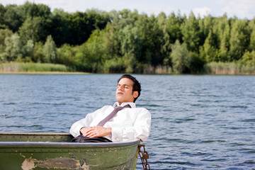 businessman lying in rowboat