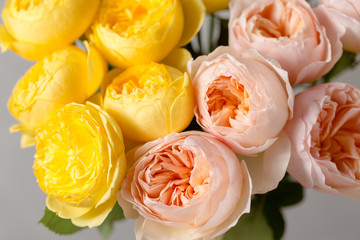 Bouquet of soft pink and yellow garden roses in a glass vase. Floral still life. close-up