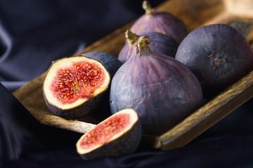Several ripe purple figs in wooden bowl on purple backdrop