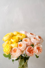 Bouquet of soft pink and yellow garden roses in a glass vase. Floral still life.