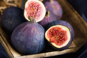 Close up on blue ripe figs in wooden bowl