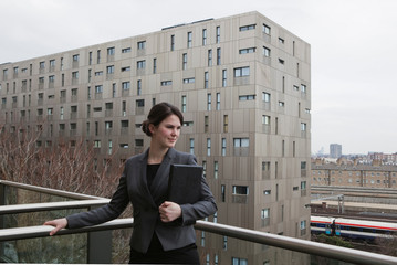 Woman standing with laptop on balcony