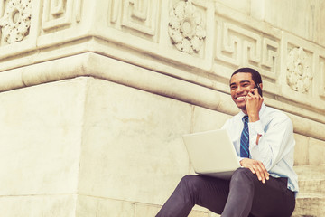 Young Happy African American Businessman working on laptop computer, talking on cell phone, smiling, sitting on stairs by marble wall outside office building in New York, wearing white shirt, tie..