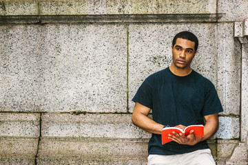 Young African American Man reading book, thinking, relaxing outside in New York, wearing black T shirt, standing against concrete wall, holding red book, looking away, serious, sad, lost in thought..