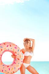 Summer Vacation. Enjoying suntan woman in white bikini with donut mattress near the ocean.