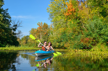 Family kayaking, mother and child paddling in kayak on river canoe tour, active autumn weekend and vacation, sport and fitness concept